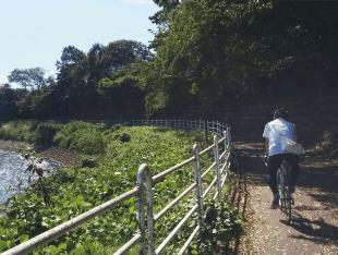 川沿いをサイクリングする人