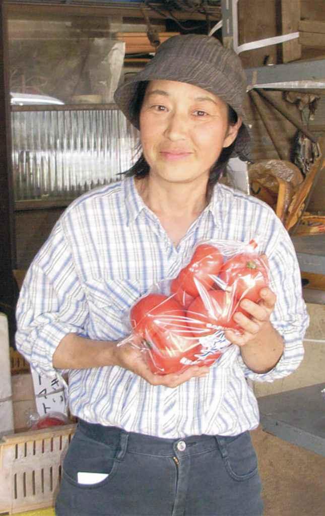 熟成の進んだ「ジュース用」のトマトを手にした石井英子さん。